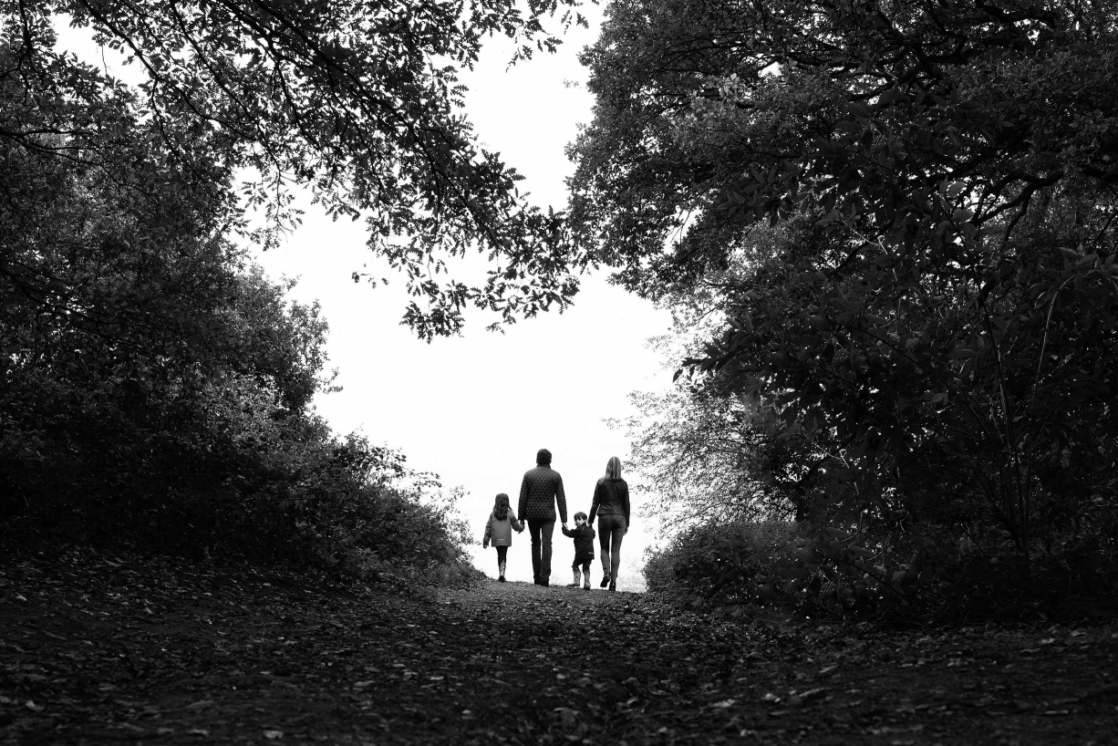 Trees and a pathway surround this family silhouette in a dramatic family portrait composition by London professional photographer Helen Bartlett.