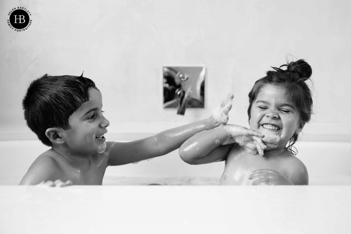 Siblings play in the bath during family photography in Wandsworth.