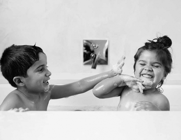 Family photography in Wandsworth with a brother and sister playing in a bubble bath.
