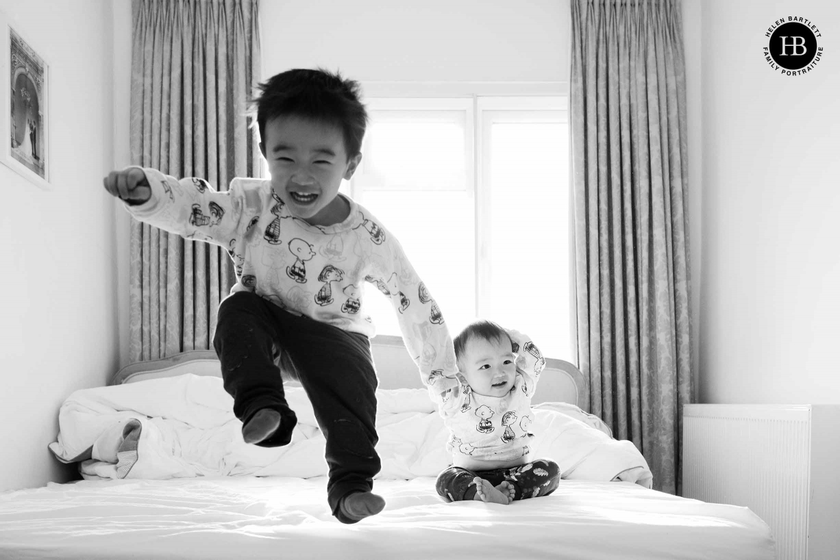 Toddler jumps on the bed while baby brother looks on