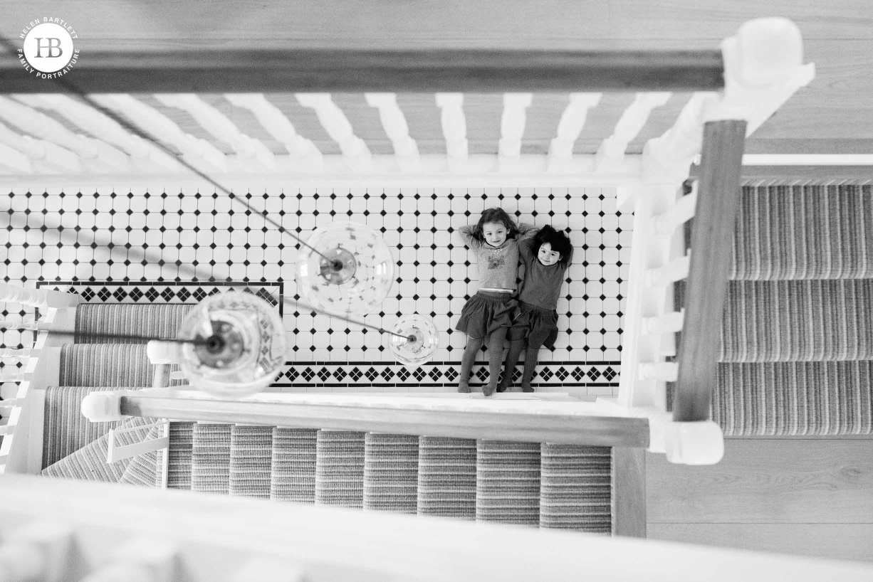 Family photography at home: two girls lie on the hall floor looking up at the photographer. The image is taken from three floors up and the stairs spiral around showing the interior of their London home