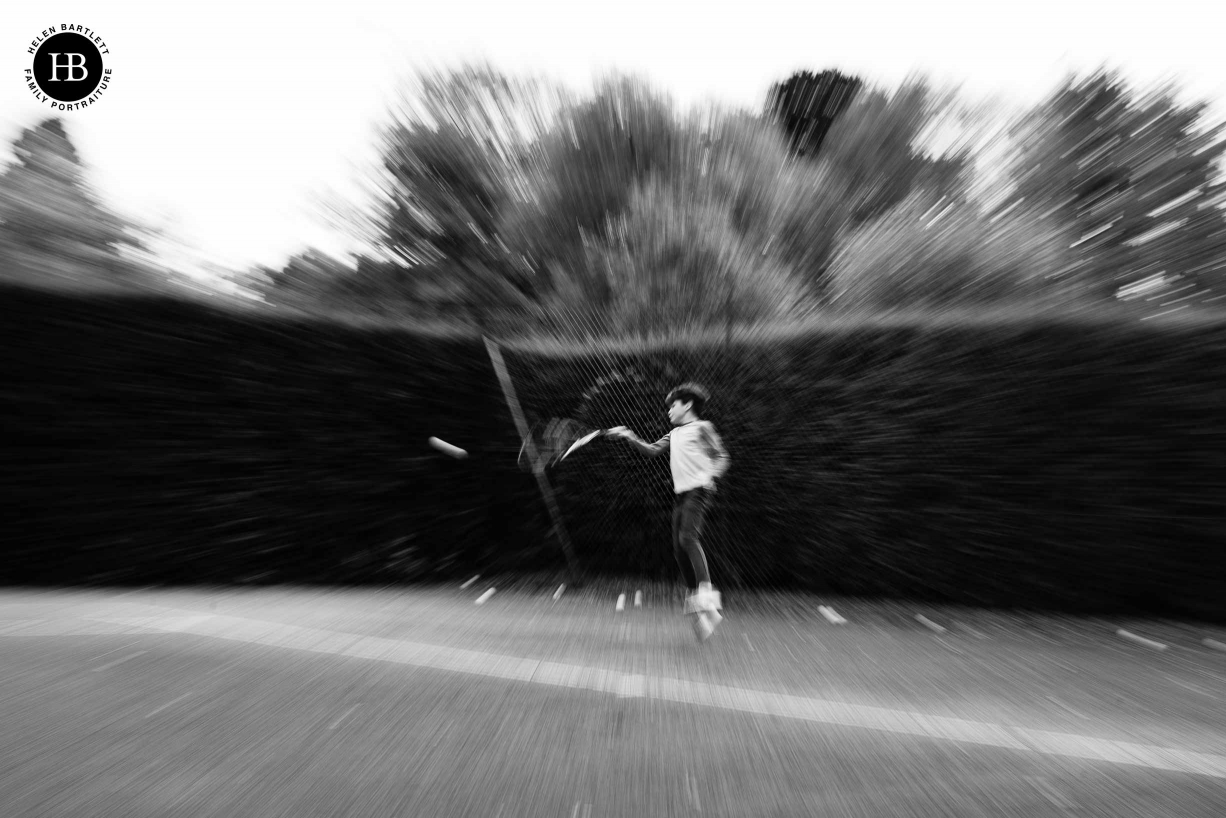 teenage boy photographed playing tennis with zoom burst