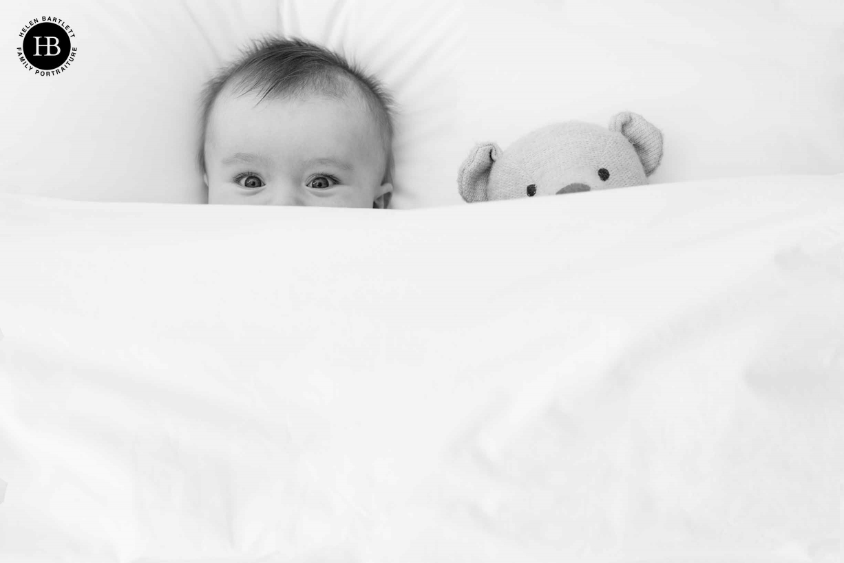 baby and teddy bear peek over the sheets