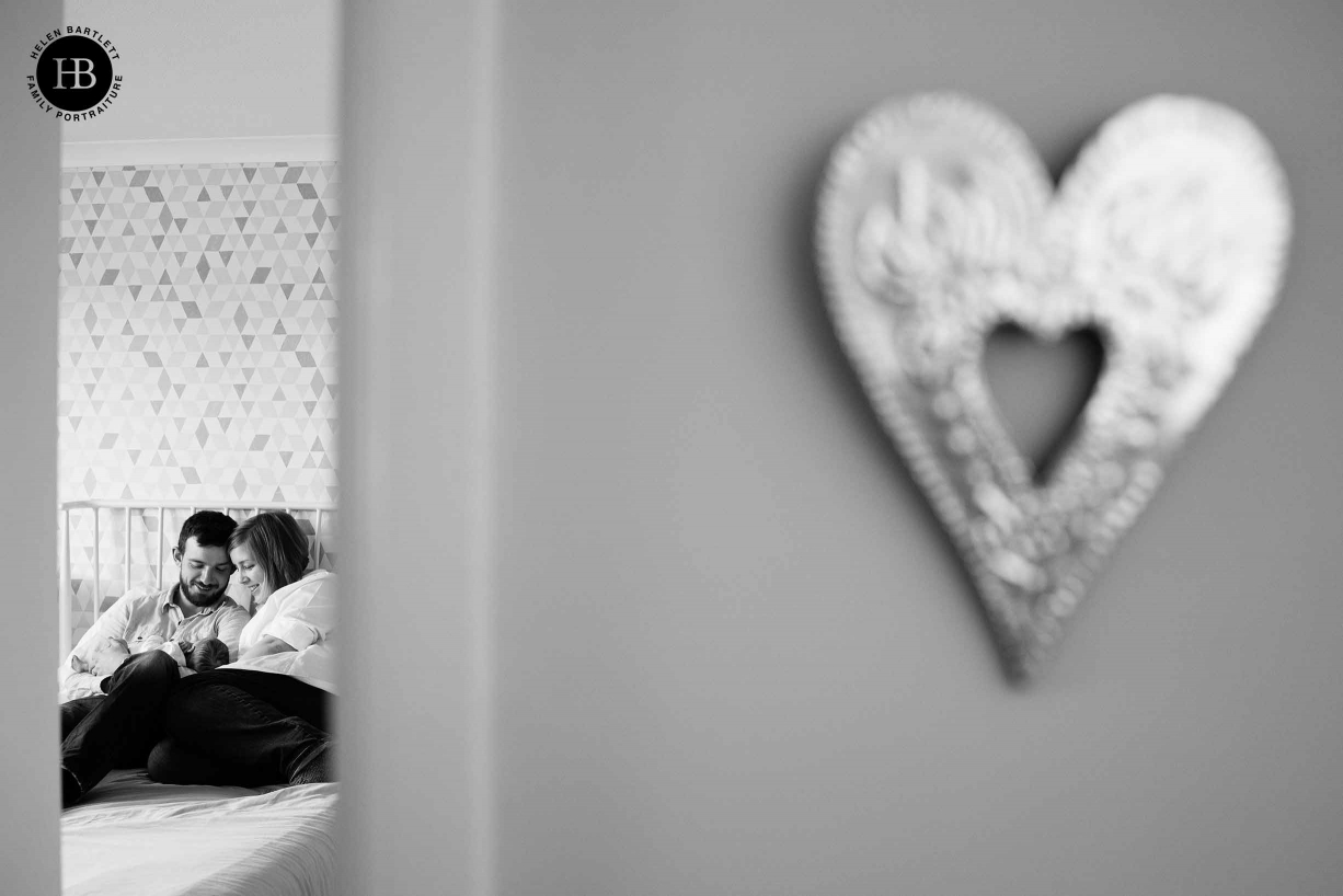 parents and newborn photographed from outside their bedroom. Heart ornament on the wall balances the composition