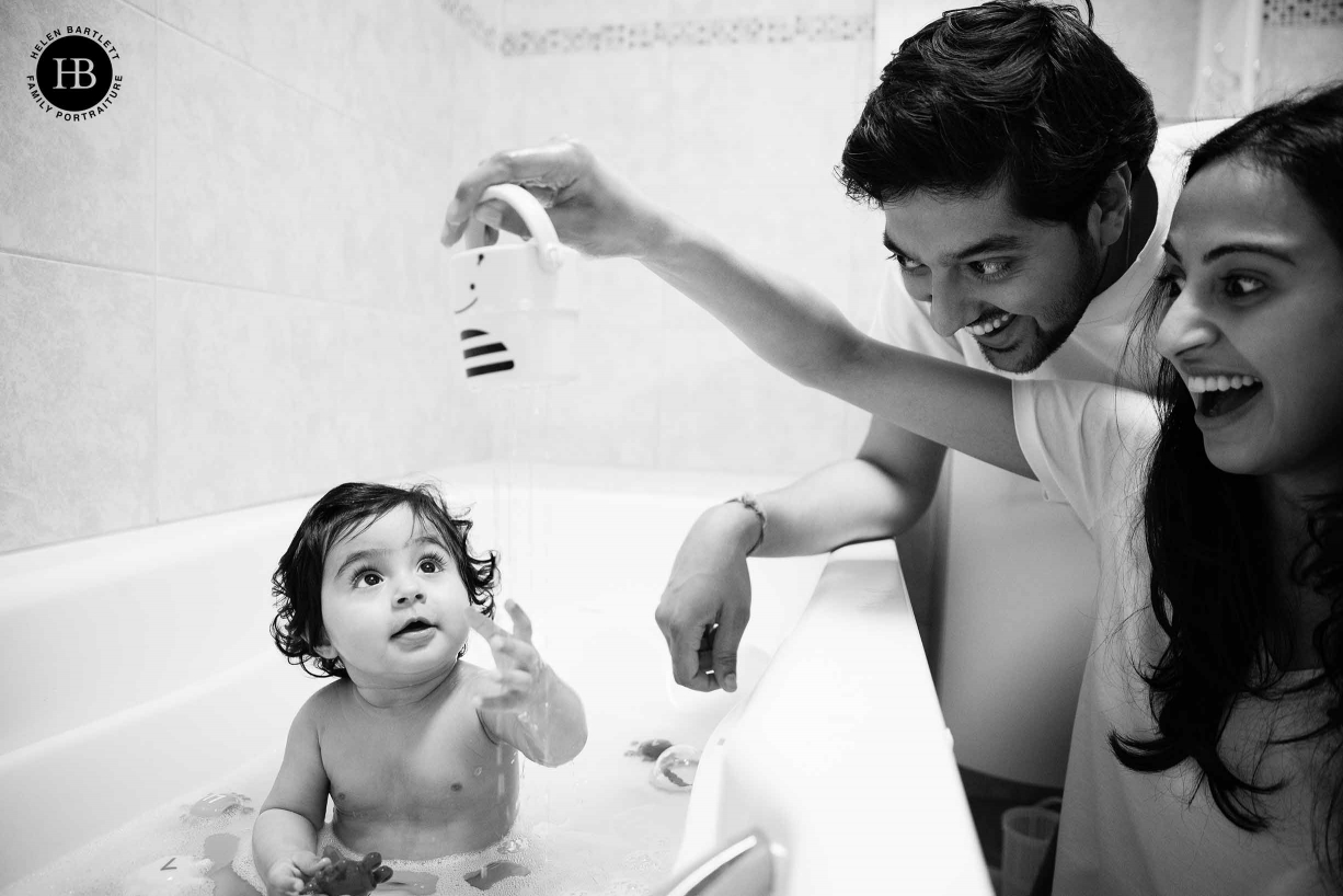 parents play with their daughter as she has a bath. photo by photographer Helen Barltlett
