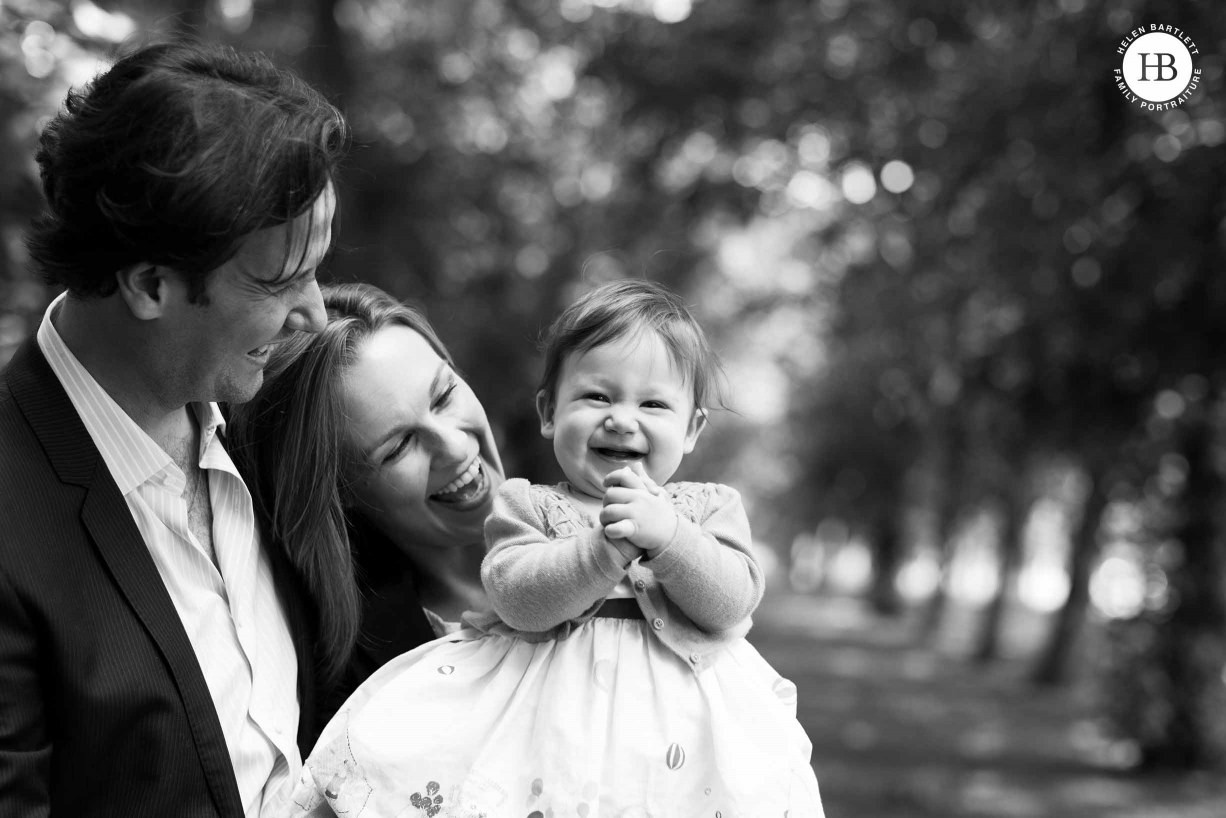 baby claps her hands with joy while being held by her parents at the park