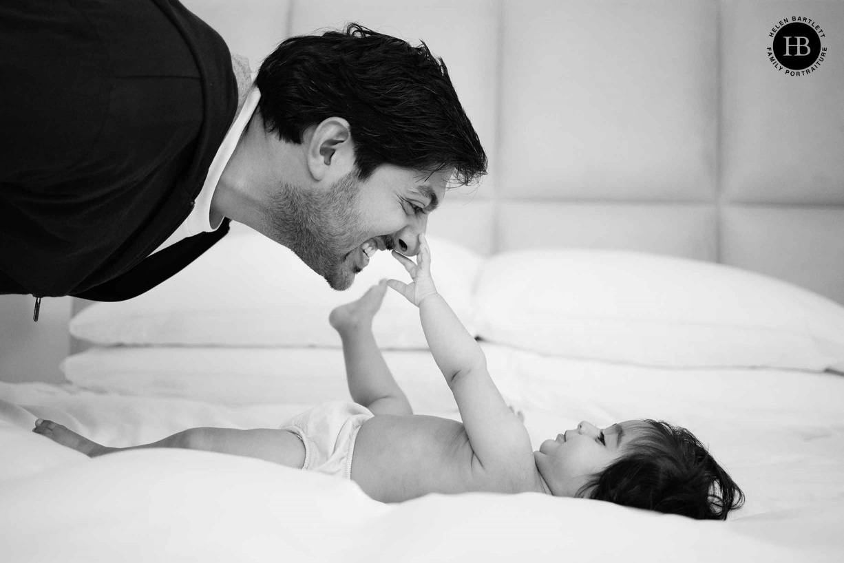 father plays a game with his baby daughter, she is reaching up to hold his nose