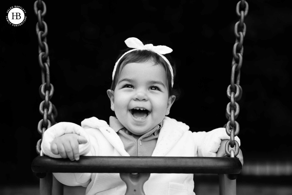 girl laughs with joy on a swing on her first birthday