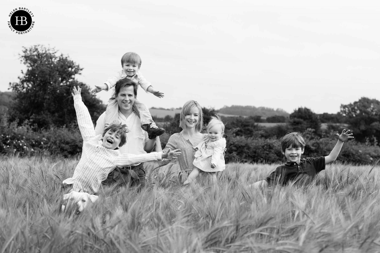family-laugh-together-in-field-professional-family-photo