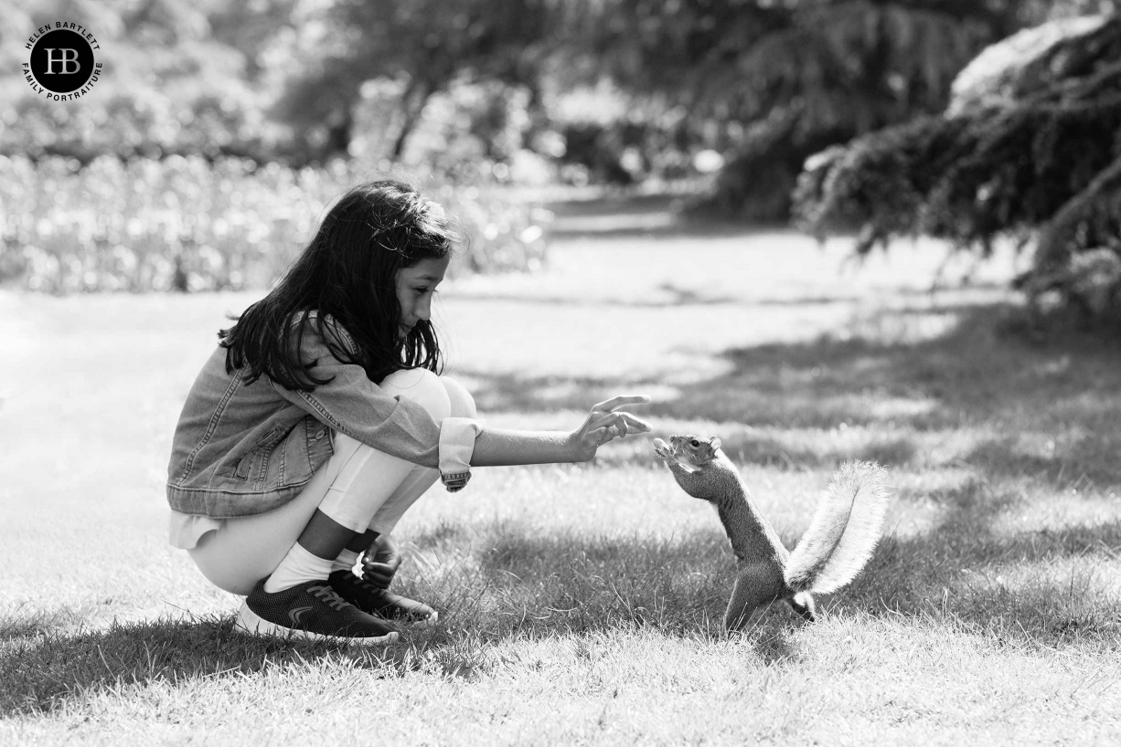 girl-feeds-squirrel-in-park