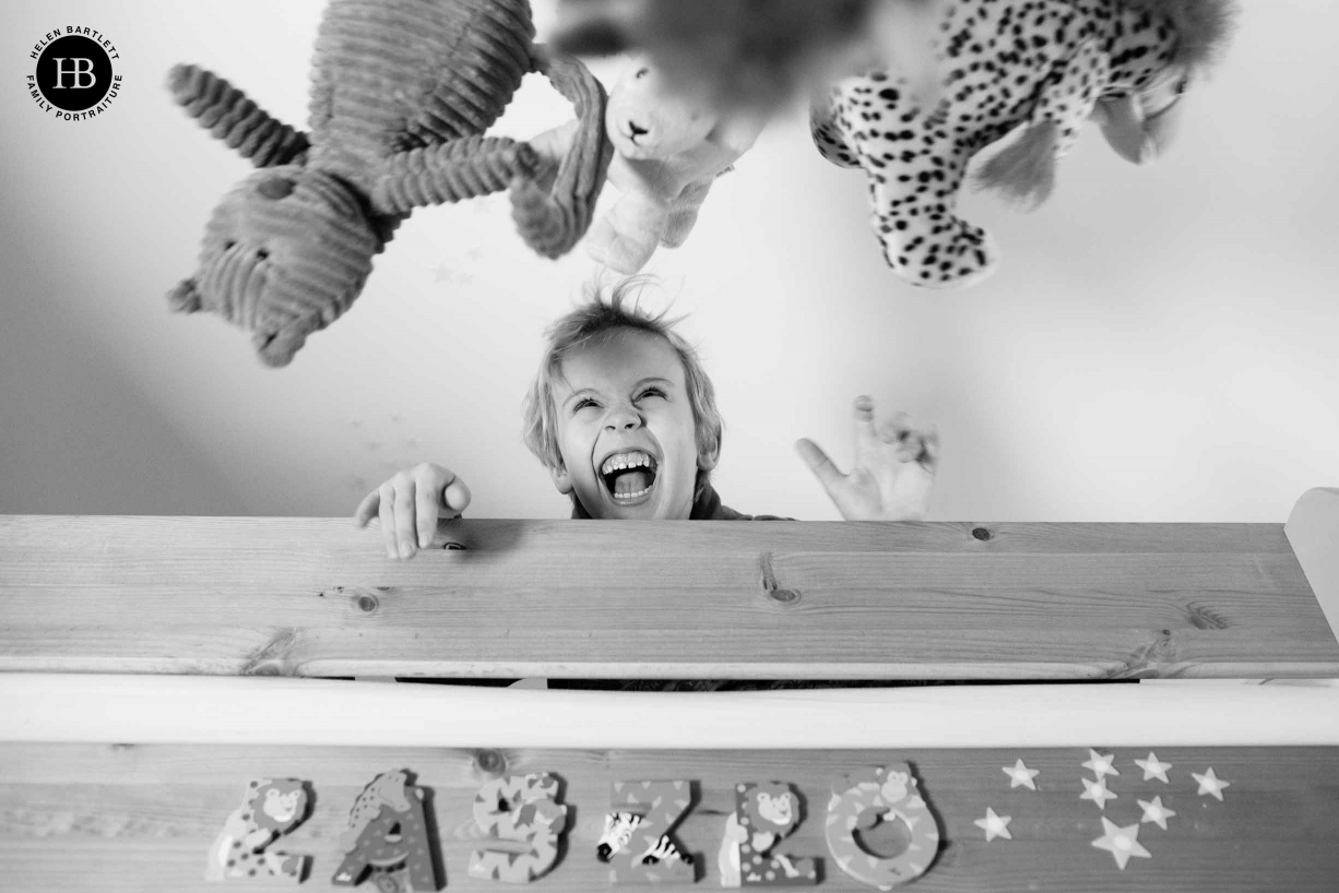 A boy plays in his bedroom, throwing his toys in the air during his family photo shoot