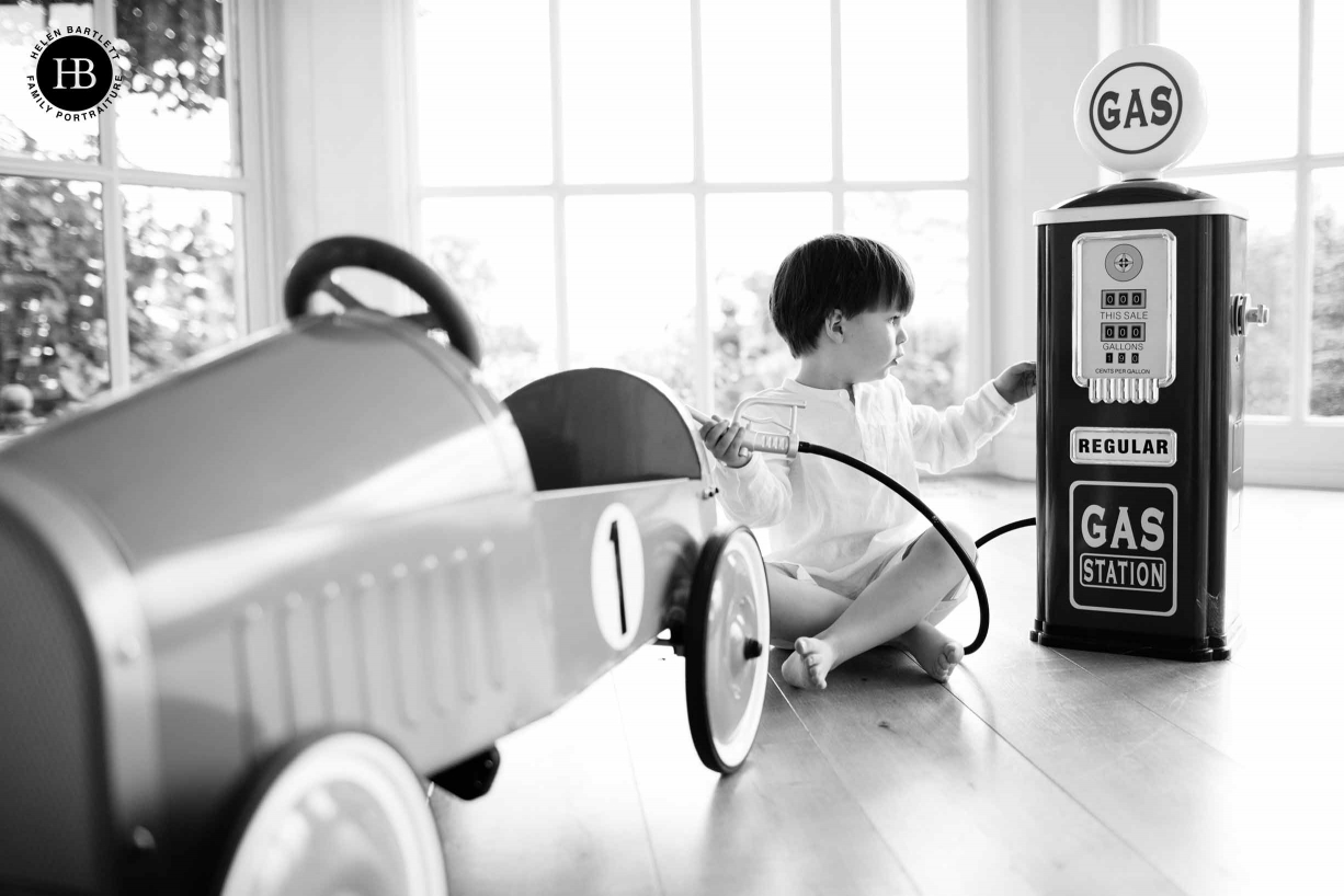 A boy plays with his toy car during a family photoshoot in his home
