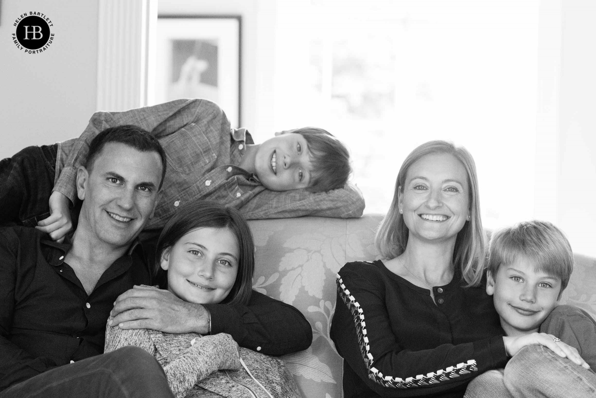 Formal family portrait of mum, dad, and three teenagers on sofa in London home