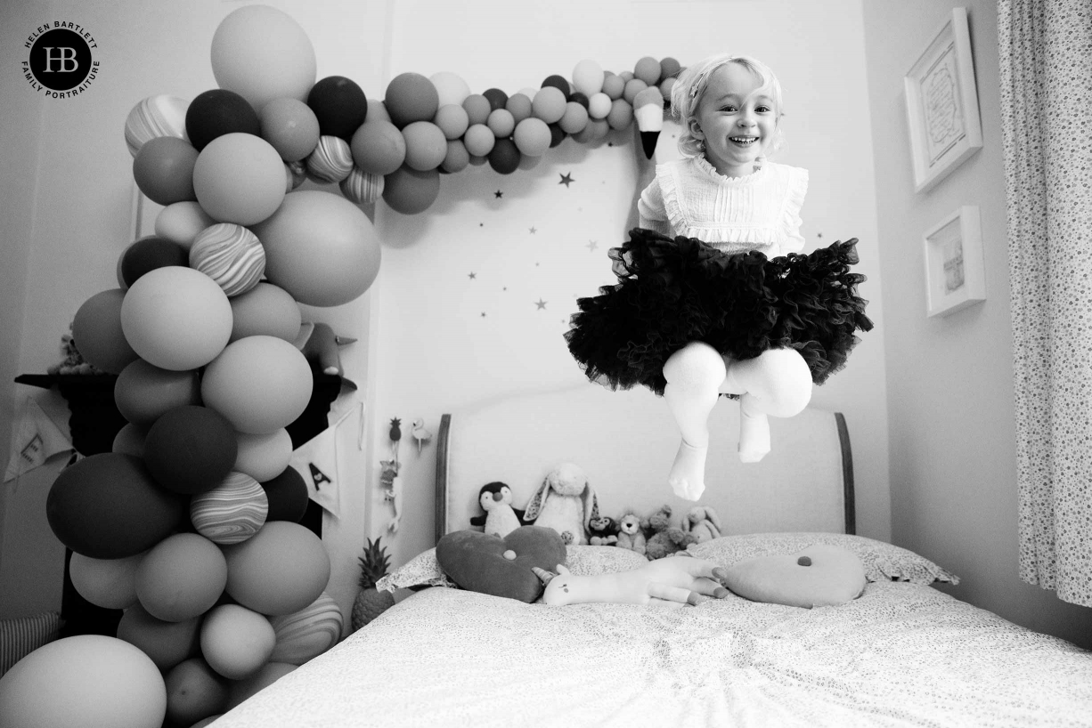 Girl jumping on the bed in her bedroom with balloons in the background. This is an example of family photography at home in London.