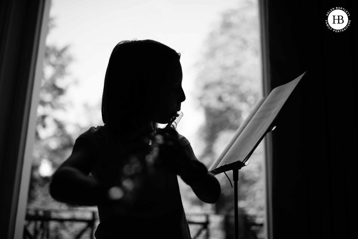 A home photo shoot: a girl practises her flute and is photographed in silhouette.