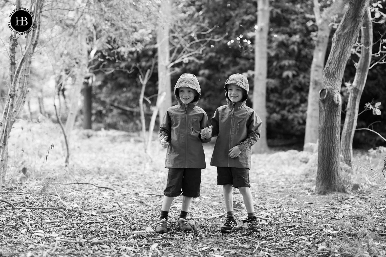 Twin boys play in the rain in their garden