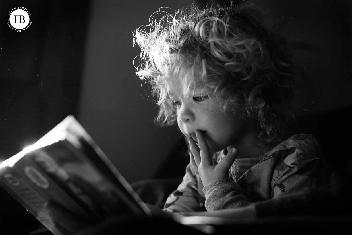 A child reads a book by the window on the family sofa. It was one of a family photography at home session.