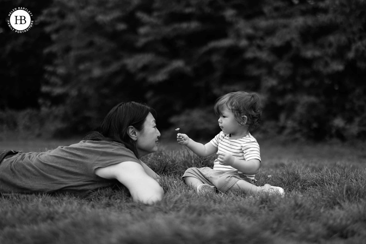 One year old baby offers a buttercup to mother who is lying on the grass with him. Black and white image with shallow depth of field.