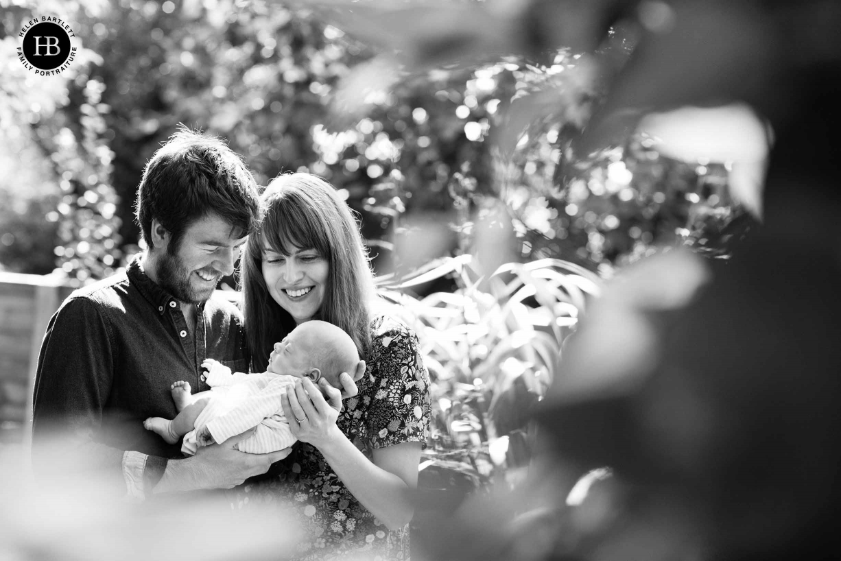 Leaves and bushes are used as a framing device in a newborn and family portrait taken in the clients garden