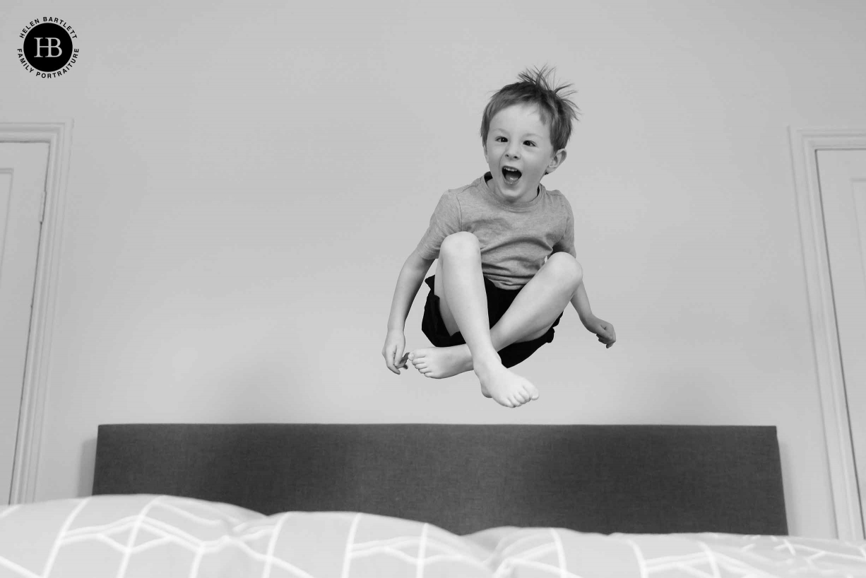 Little boy jumps on a bed, he is caught mid-air with his legs crossed. Showing the face-tracking autofocus of Canon EOS R5