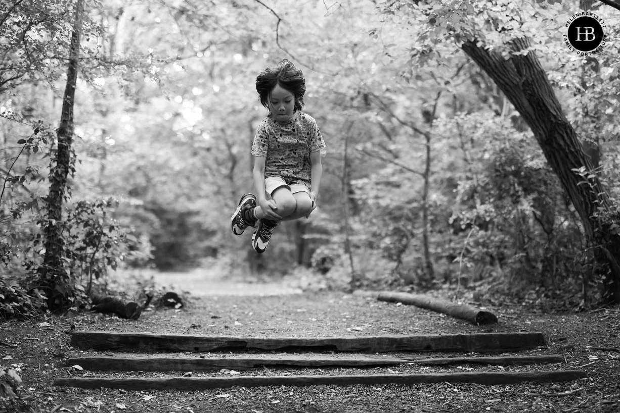 Boy caught mid-air as he jumps with his legs tucked up. Image used to show amazing tracking focus of Canon EOS R5 at wide apertures.