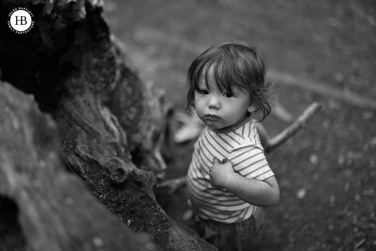 Little boy looks up and points to himself. He's playing with mud and sticks by a fallen tree.