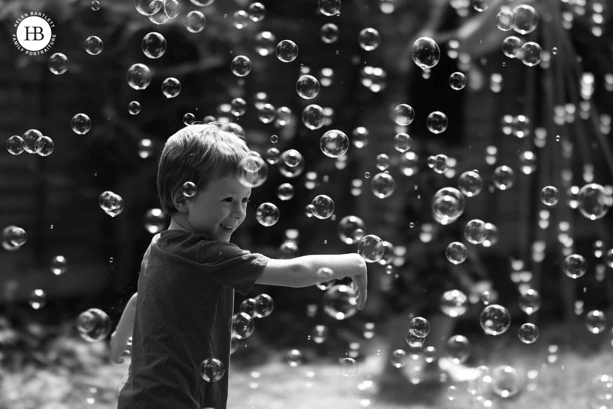 Little boy joyfully plays amongst bubbles.