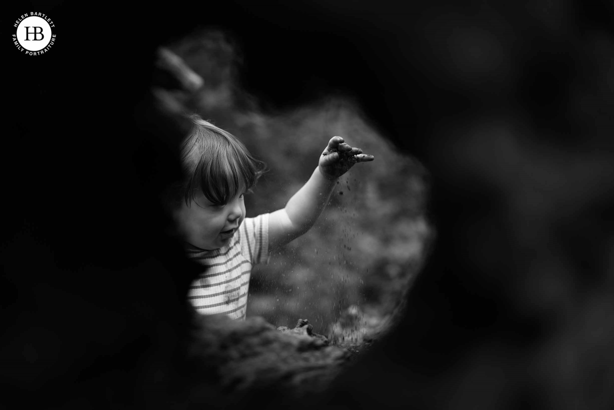 Little boy plays with mud and drops grains of mud and sand from his hand. Shot through a hole in a fallen tree for an interesting composition showing the benefits of the vari-angle screen on the EOS R5