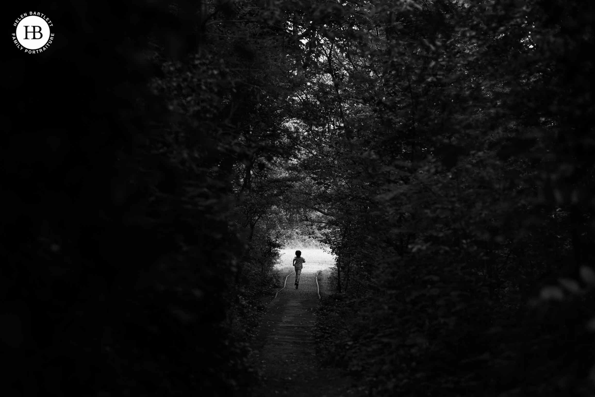Boy running through a tunnel of undergrowth to the light field beyond, black and white