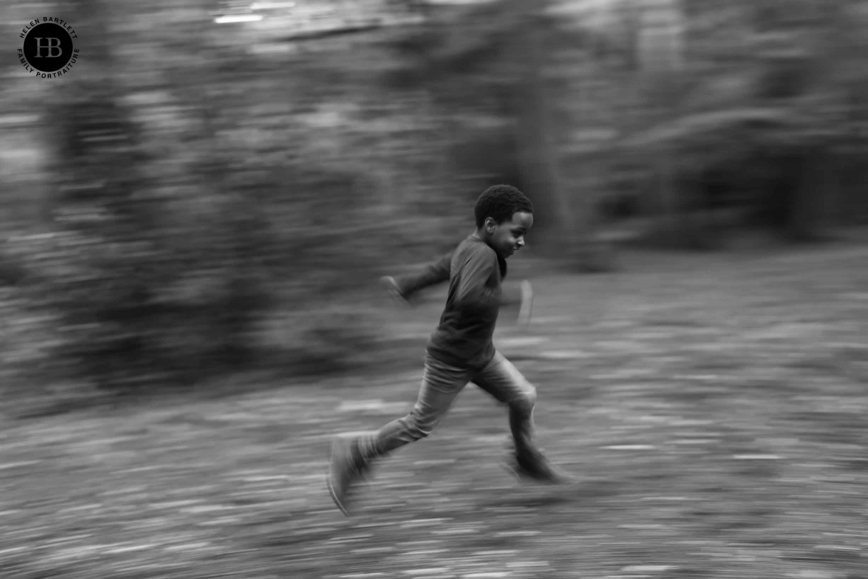 Little boy runs through the wood. Image shot with a slow shutter speed of 1/20 and panning for visual effect.