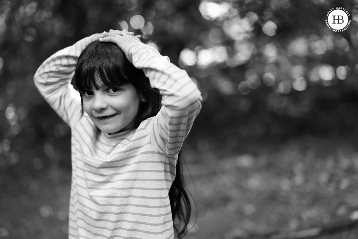 Portrait of a girl laughing up at the camera with hands on her head. Image to demonstrate lovely tones and fabulous detail in Canon EOS R5 files.