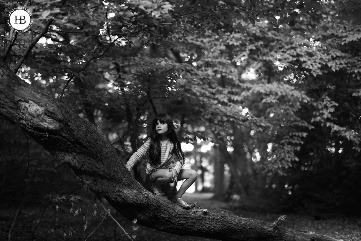Little girl crouches on a tree trunk in a forest. Image shows incredible tones and dynamic range of 45mp EOS R5 files