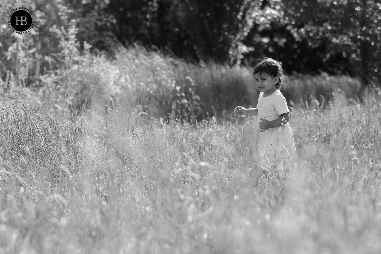Girl walks through long grass. Image is backlit and shows the way Canon EOS R5 picks out detail in the grass and also focuses at very wide apertures.