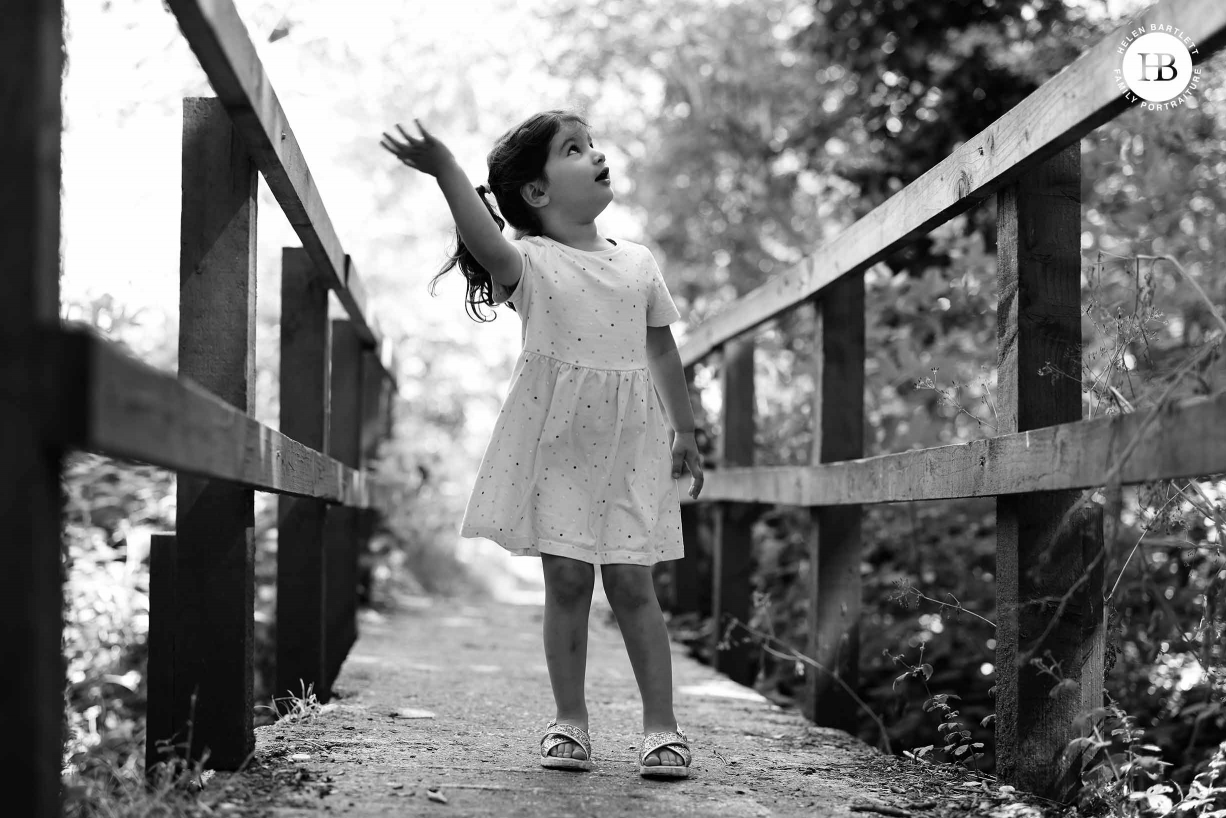 Little girl stands on a wooden bridge looking up and waving.