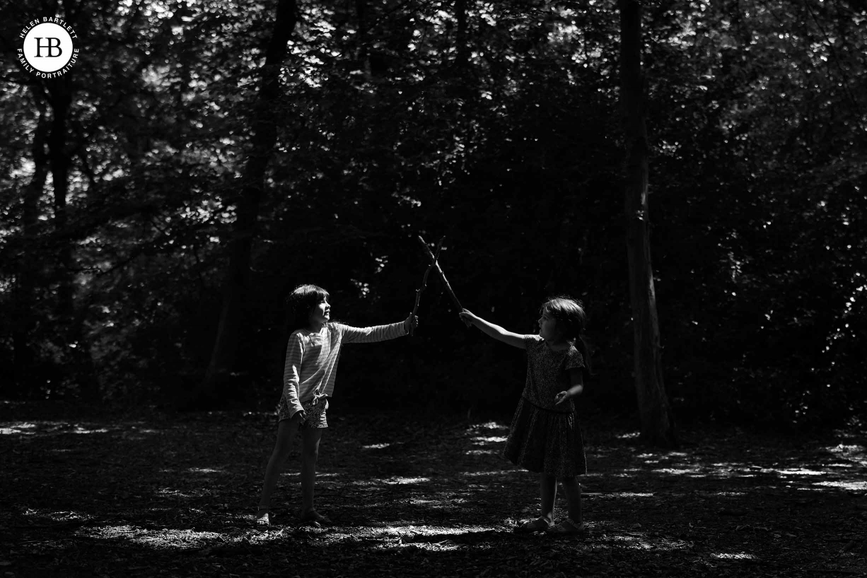 Two girls sword fight in a patch of sunlight in the woods. High contrast, dark image to show how the EOS R5 focuses well in difficult lighting conditions.