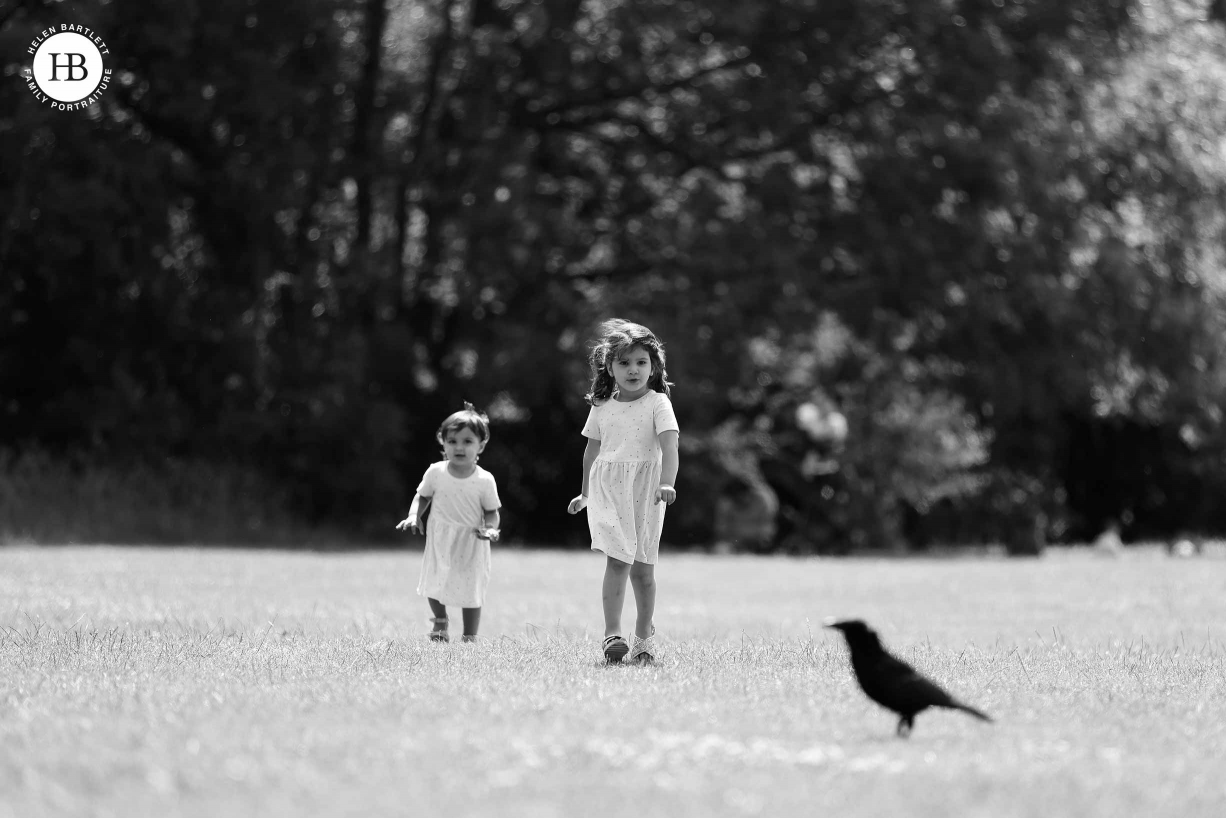 Two girls walk across field towards the silhouette of a bird. Image included to show high quality images using the adaptor on Canon EOS R5 and EF lenses.