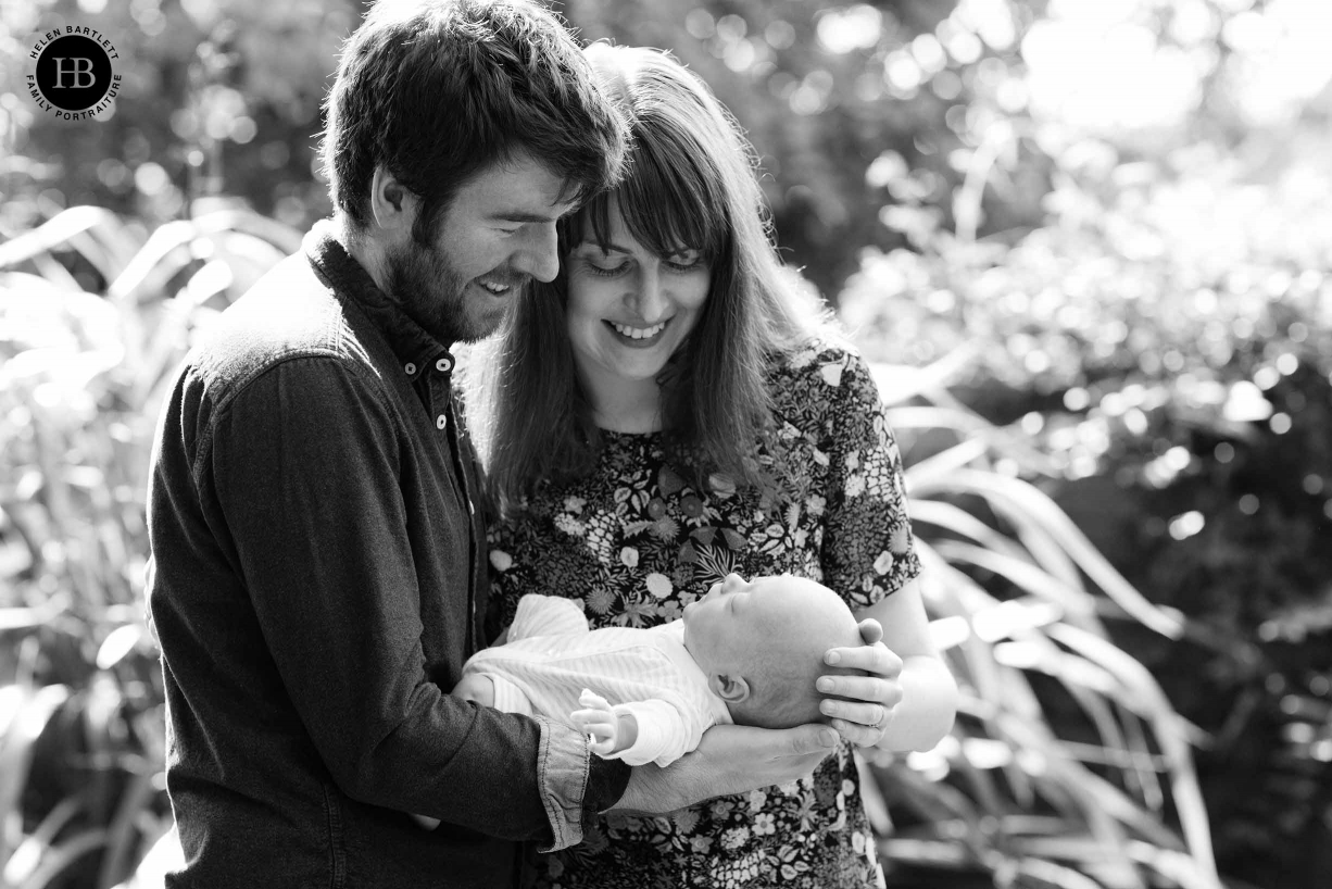 mum and dad cradle baby in garden during socially distanced outdoor newborn photography session