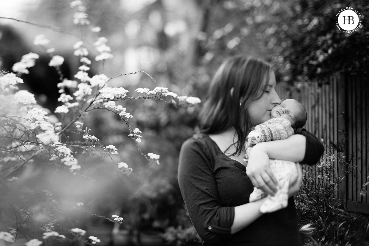 mum kisses newborn baby, beautiful flowers used as part of a creative composition in the clients garden for professional outdoor newborn session