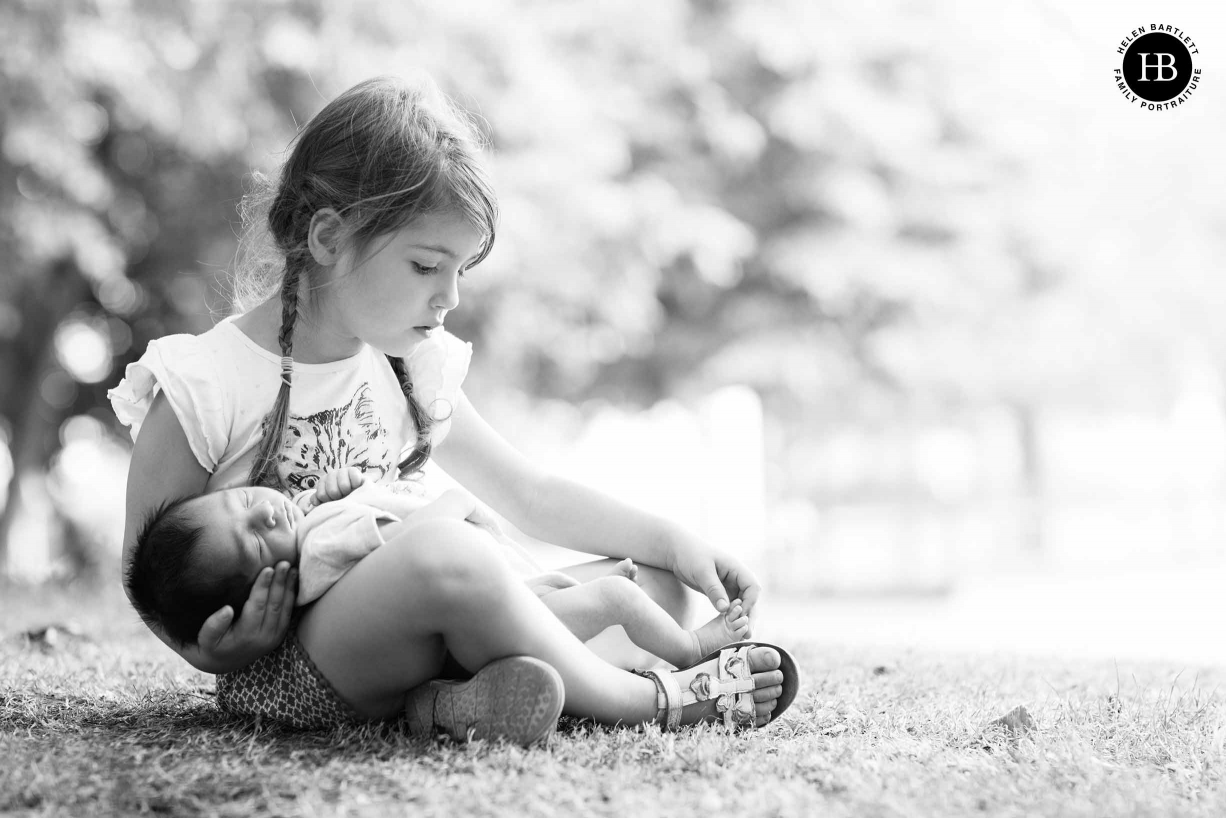 older sister cradles newborn baby brother while counting his toes. Picture taken in a London park during an socially distanced outdoor newborn photography session