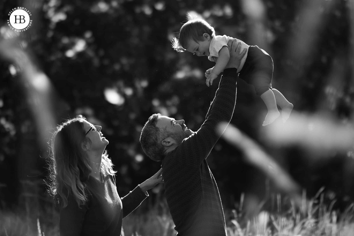 Dad, mum and baby shot in profile as dad lifts baby above his head. Backlit for beautiful effect and shot through long grass for foreground detail. Image used as an illustration for beautiful files from Canon EOS R5
