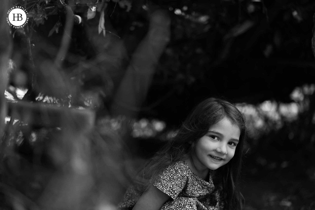 Portrait of little girl sat in a den, she smiles up at the camera.