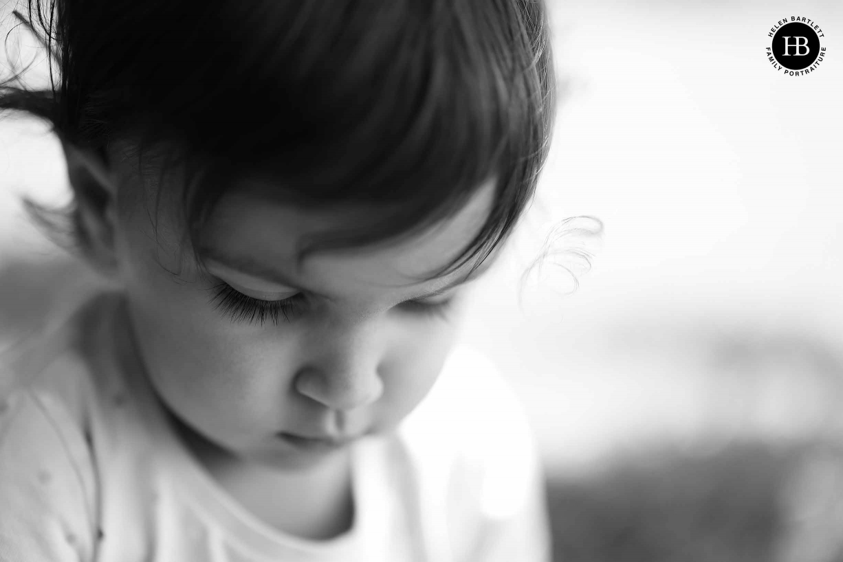 Portrait headshot of little girl with shallow depth of field to emphasis eyelashes and a beautiful curl by her face.