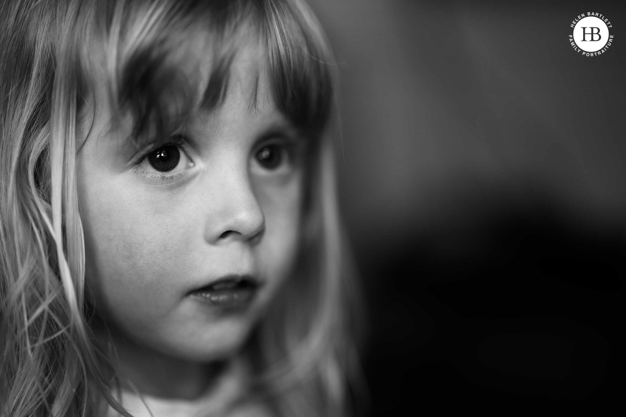 Window lit, head and shoulders, portrait of little girl in black and white.