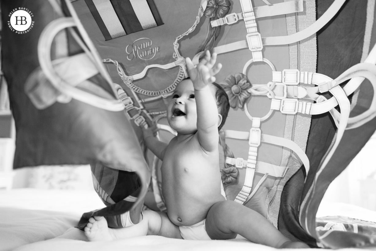 baby plays peek a boo underneath hermes scarf