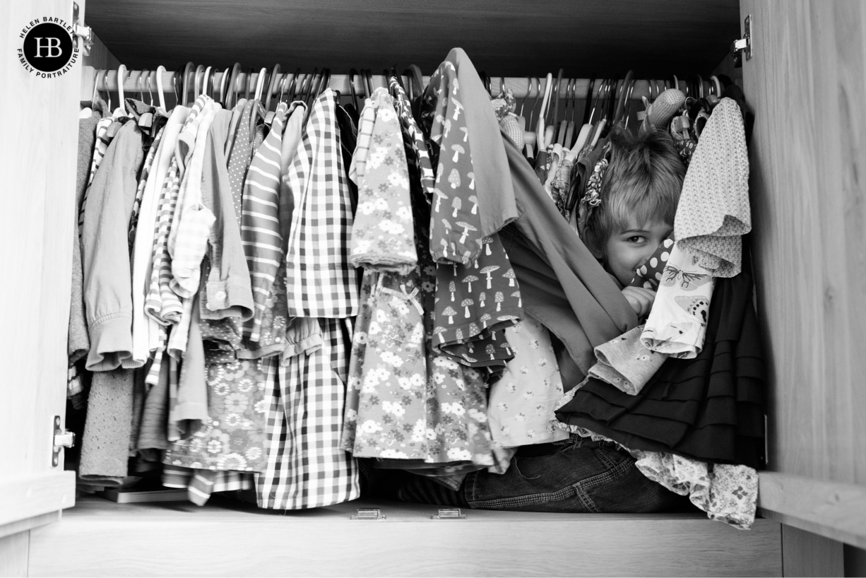 boy hides in a wardrobe during a game of hide and seek. Image used to illustrate what to wear on a family photo shoot