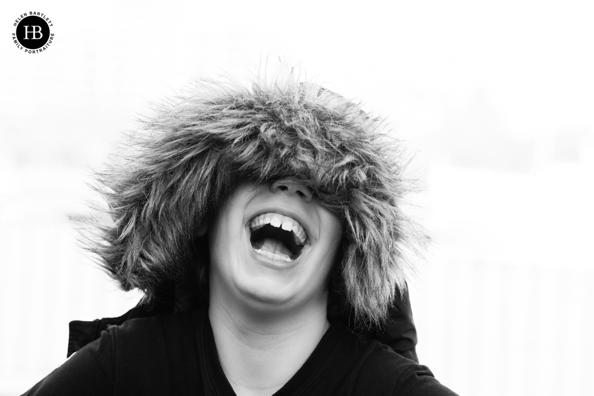 boy laughs under the hood of a parker jacket to show the benefit of warm clothing on a family photo shoot