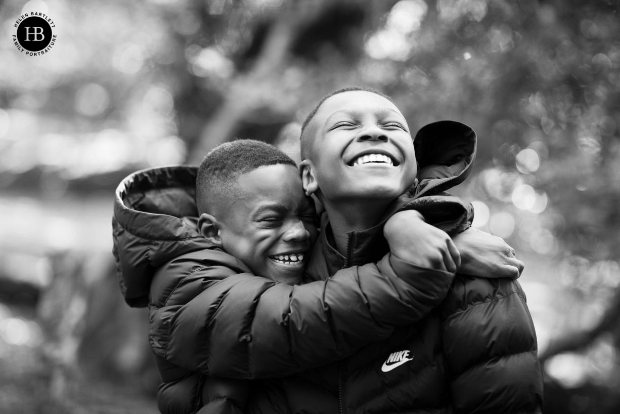 two teenage boys hug in happy photo