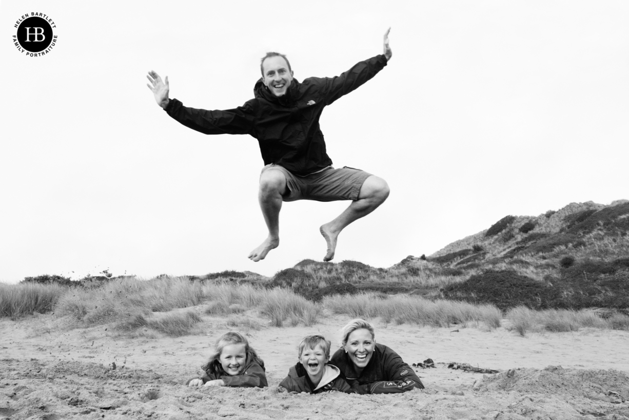 dad jumps over his family who are in a hole dug in the sand on the beach. A fun family photo