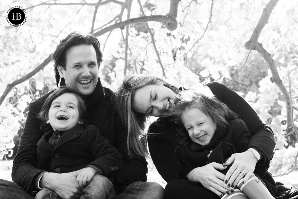 A happy family photograph taken in the autumn, low winter light shines through the trees