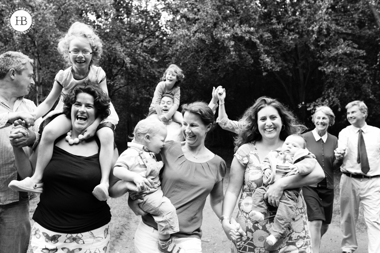 large multi-generational family photograph with everyone laughing and running towards the camera